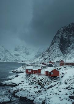 Rote hütten auf einer verschneiten insel sakrisoy, norwegen