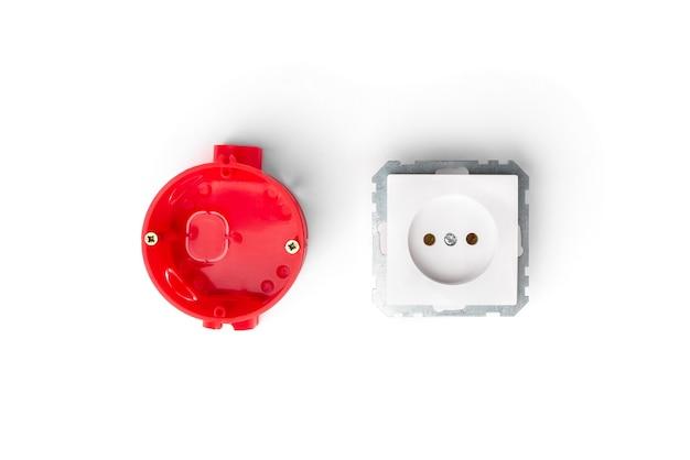 Rote installation elektrokasten für steckdosen und weiße steckdose und drähte auf betonhintergrund.