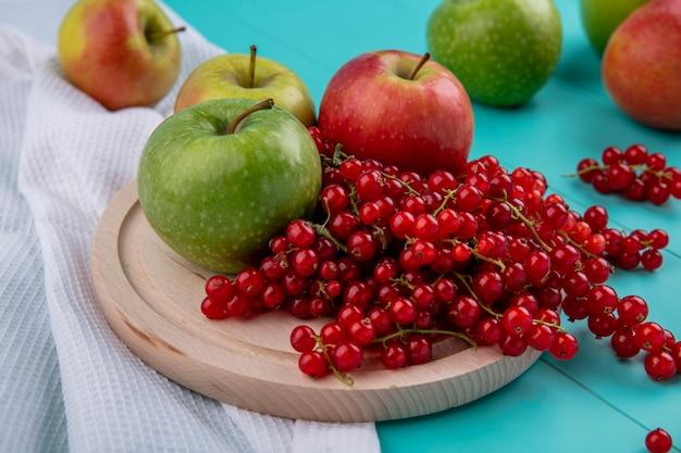Rote johannisbeere der seitenansicht mit äpfeln auf einem holzständer und einem küchentuch auf einem hellblauen hintergrund