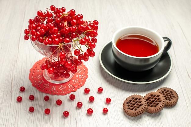 Rote johannisbeere der vorderansicht in einem kristallglas auf dem roten ovalen spitzendeckchen eine tasse tee und kekse auf dem weißen holztisch
