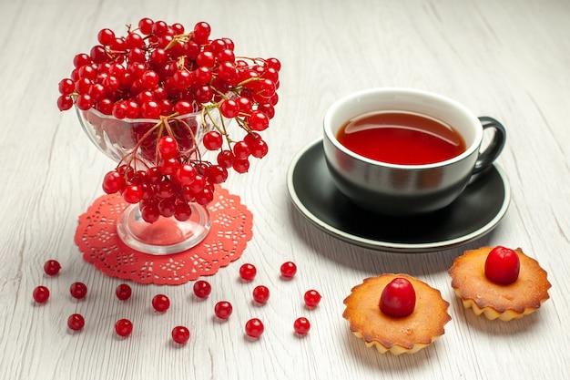 Rote johannisbeere der vorderansicht in einem kristallglas auf dem roten ovalen spitzendeckchen eine tasse tee und torten auf dem weißen holztisch