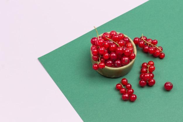 Rote johannisbeere in einer keramikbox. geometrischer rosa grüner hintergrund. flach liegen. speicherplatz kopieren