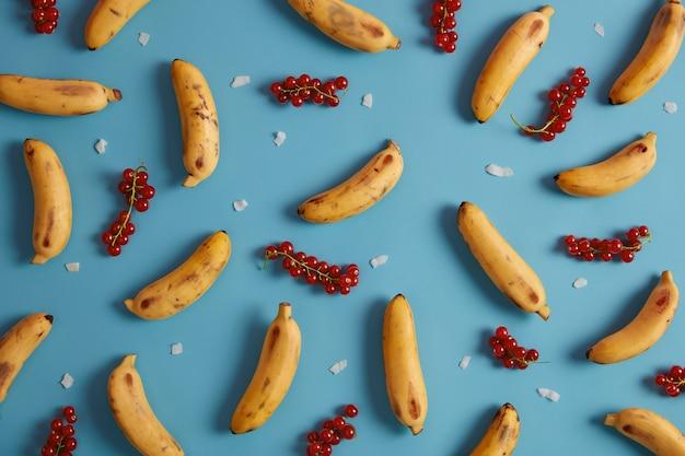 Rote johannisbeere und gelbe bananen zum servieren von kuchen, brötchenfüllung, kompott, saft, hausgemacht oder smoothie. sammlung von exotischen früchten und reifen beeren. flaches legemuster. leckere sommerfrüchte