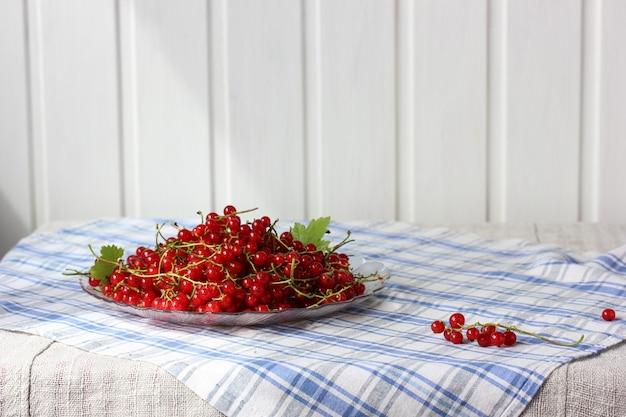 Rote johannisbeeren auf dem tisch in einem teller
