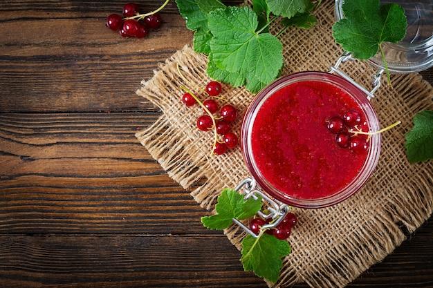 Rote johannisbeermarmelade in einem glas auf einer holzoberfläche. leckeres essen.