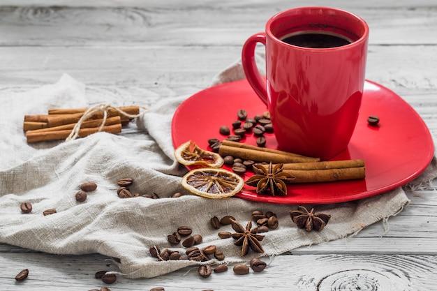 Rote kaffeetasse auf einem teller, hölzerner hintergrund, getränk, weihnachtsmorgen