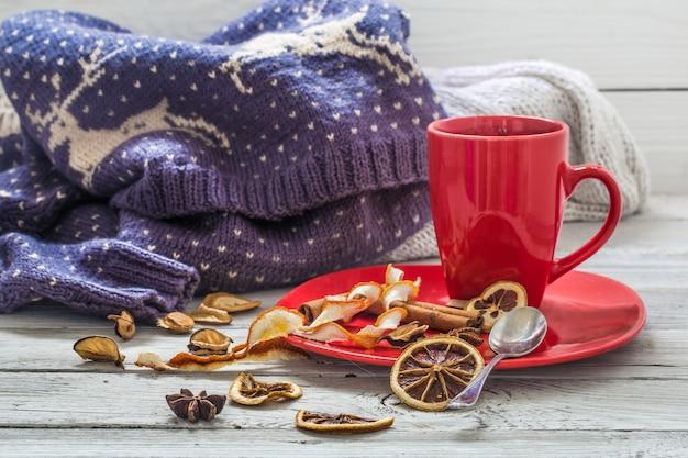 Rote kaffeetasse auf einem teller, holztisch, getränk, weihnachtsmorgen