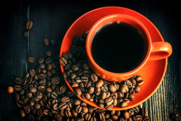 Rote kaffeetasse auf hölzernem schreibtisch, kaffeestimmung