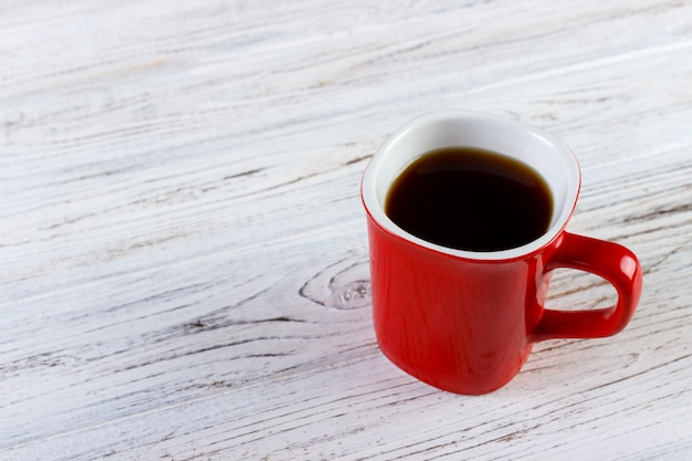 Rote kaffeetasse auf holztisch.