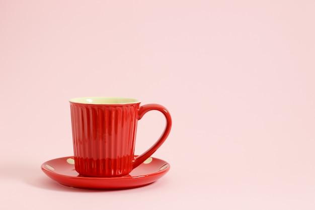 Rote kaffeetasse auf roter platte über rosa hintergrund.