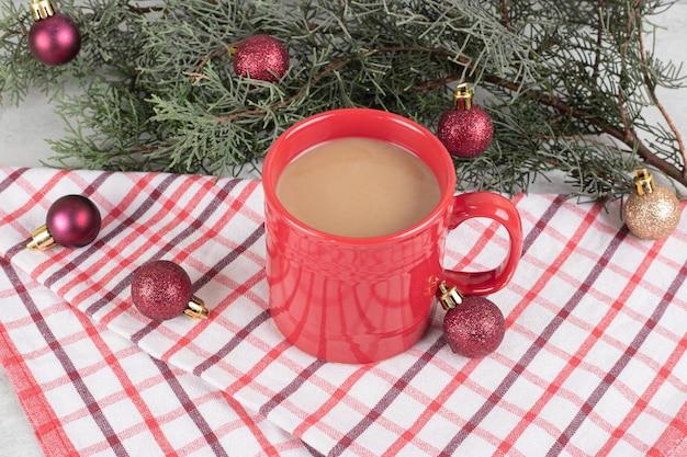 Rote kaffeetasse auf tischdecke mit weihnachtskugeln und tannenzweig