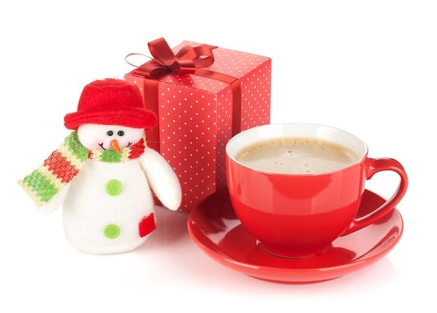 Rote kaffeetasse, geschenkbox und schneemannspielzeug. isoliert auf weißem hintergrund
