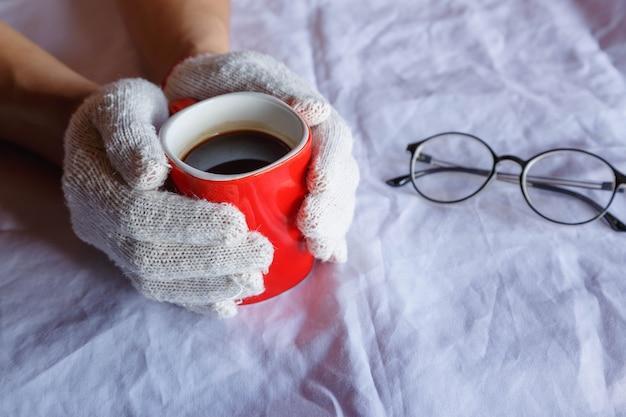 Rote kaffeetasse in der hand, die handschuhe im winter trägt