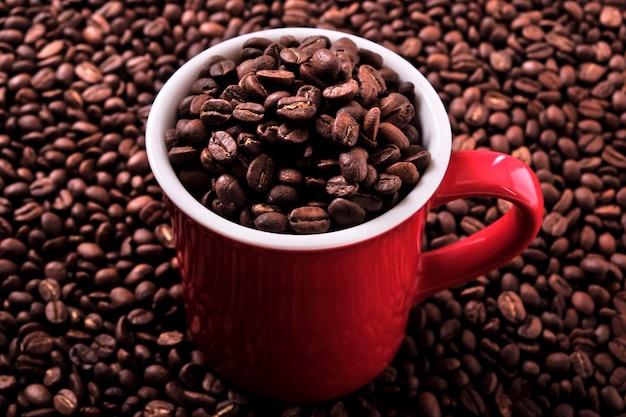 Rote kaffeetasse mit bohnen gefüllt