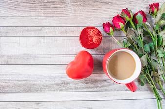 Rote Kaffeetasse mit Herzen und rosafarbenem Valentinsgruß-Tageskonzept