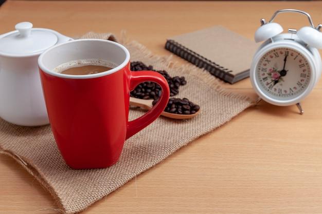 Rote kaffeetasse mit kaffeebohnen und weißem wecker auf geschäftstabelle