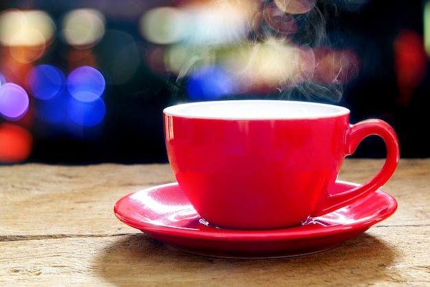 Rote kaffeetasse mit rauch auf verschwommenen lichtern