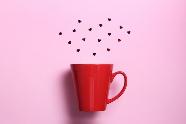Rote kaffeetasse mit roten funkelnherzen auf rosa wand. flache laienzusammensetzung. romantisch, st. valentinstag-konzept.