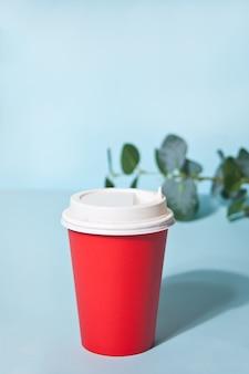 Rote kaffeetasse und heimische pflanze zum mitnehmen
