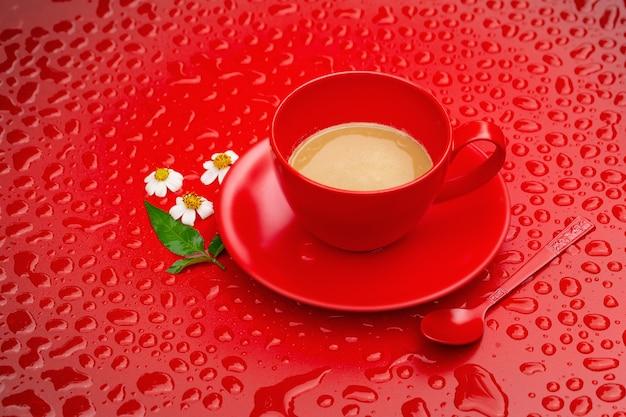 Rote kaffeetasse und kleine blumen auf rotem blackground
