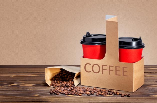 Rote kaffeetassen in karton und beutel mit bohnen