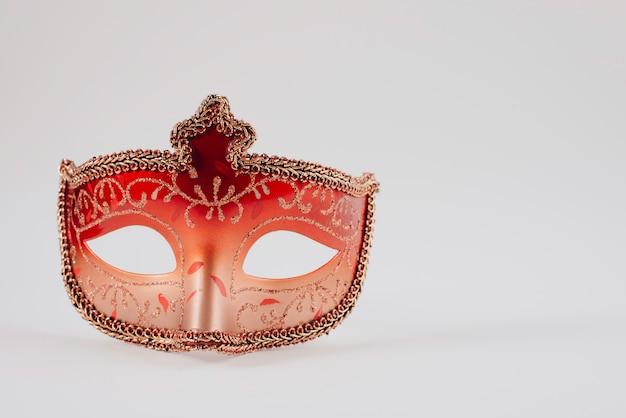 Rote karnevalsmaske auf weißer tabelle