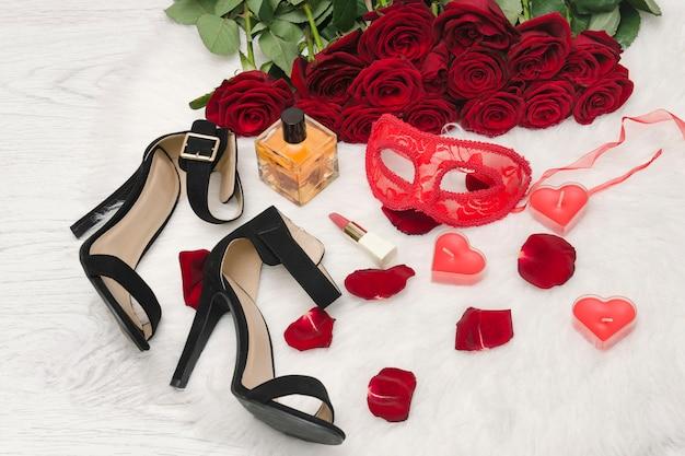 Rote karnevalsmaske, ein strauß roter rosen, schwarze schuhe mit absätzen, kerzen in form eines herzens, lippenstift, parfümflasche und verstreute blütenblätter auf dem weißen fell.