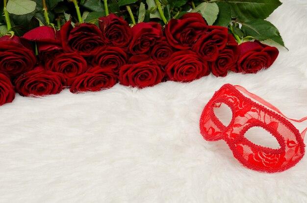 Rote karnevalsmaske liegt weißes fell in der oberfläche eines rosenstraußes