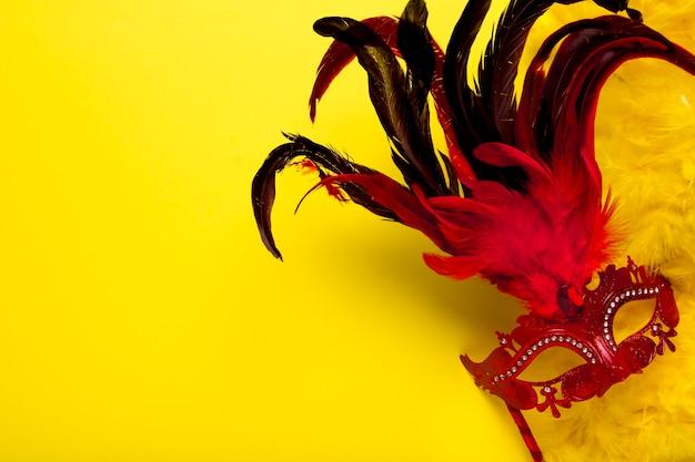 Rote karnevalsmaske mit federn und kopienraum
