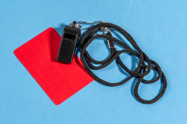 Rote karte und schiedsrichterpfeife mit platz für text auf blauem hintergrund