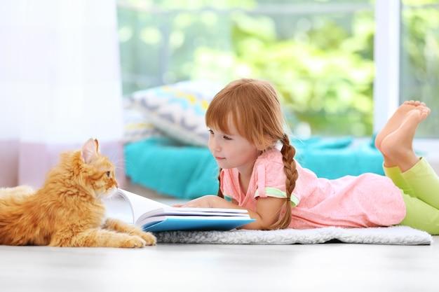 Rote katze und süßes kleines mädchen, das buch auf teppich liest