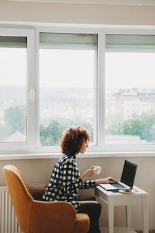 Rote kaukasische geschäftsfrau mit den lockigen haaren, die fern am computer nahe dem fenster arbeitet, trinkt einen tee und isst ein sandwich