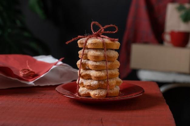 Rote keksgeschenkschwarzhintergrundtellertisch-backbäckerei