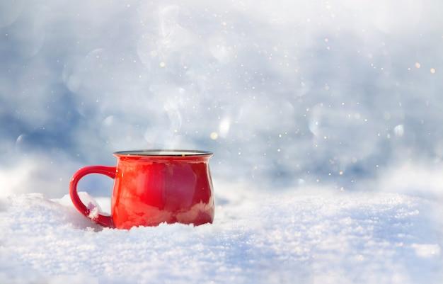 Rote keramiktasse mit heißem tee steht an einem sonnigen tag auf dem schnee