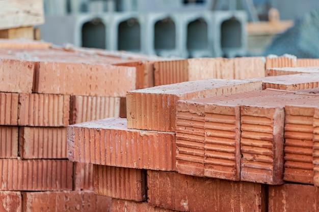 Rote keramikziegel gestapelt auf einer baustelle. baumaterialien. roter backstein für den bau eines hauses.