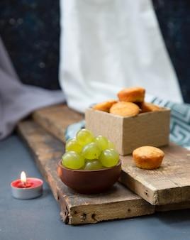 Rote kerze, eine schachtel muffins und grüne trauben auf einem stück holz