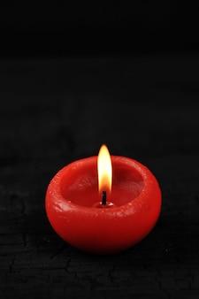 Rote kerze mit brennendem feuer auf schwarzem