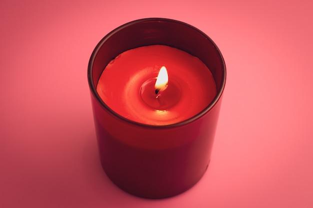 Rote kerze mit flamme auf rosa hintergrund. aromatherapie, entspannungskonzept.