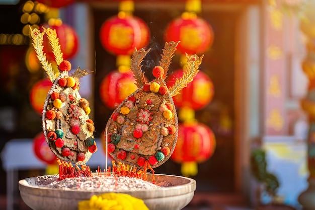 Rote kerzen und brennende räucherstäbchen im chinesischen schrein