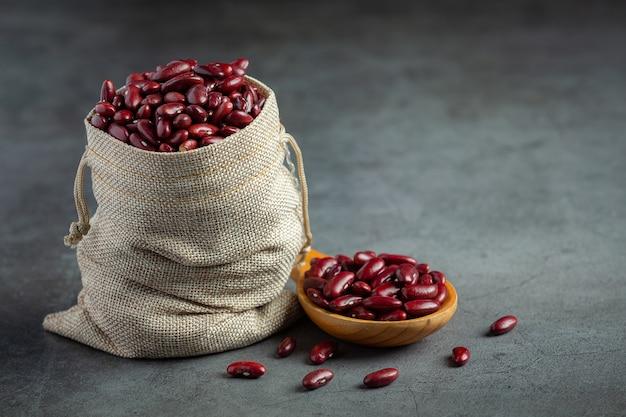 Rote kidneybohnen im sackbeutel und mit holzlöffel