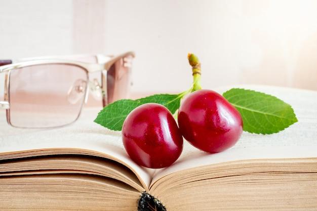 Rote kirschbeeren und gläser auf dem buch. lesen sie ihr lieblingsbuch_