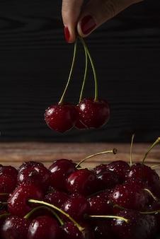 Rote kirschen in der hand genommen von der platte auf dunklem hintergrund