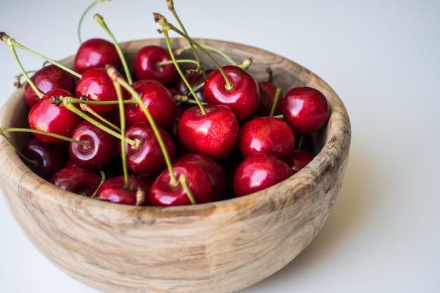 Rote kirschen in der hölzernen schüssel