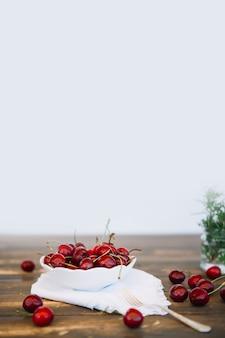 Rote kirschen in der schüssel auf die holztischoberseite