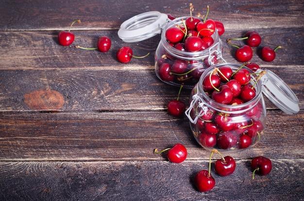 Rote kirschen in einem glasgefäß auf dunklem hölzernem hintergrund mit kopienraum. sonniges sommer- und erntekonzept.