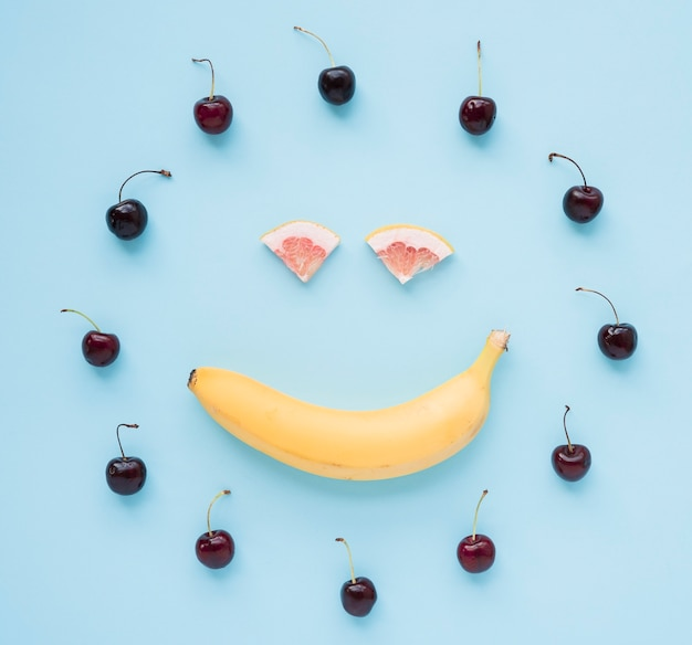 Rote kirschen vereinbarten im kreisrahmen mit dem smileygesicht, das mit banane und pampelmuse auf blauem hintergrund gemacht wurde
