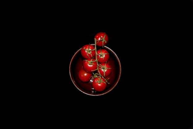 Rote kirschtomaten auf dem teller lokalisiert auf der schwarzen oberfläche
