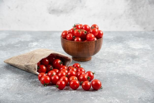 Rote kirschtomaten aus einem rustikalen korb und in einer holzschale auf marmortisch.