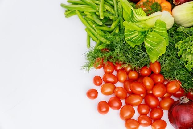 Rote kirschtomaten, grüne erbsen und dill auf weißem tisch.