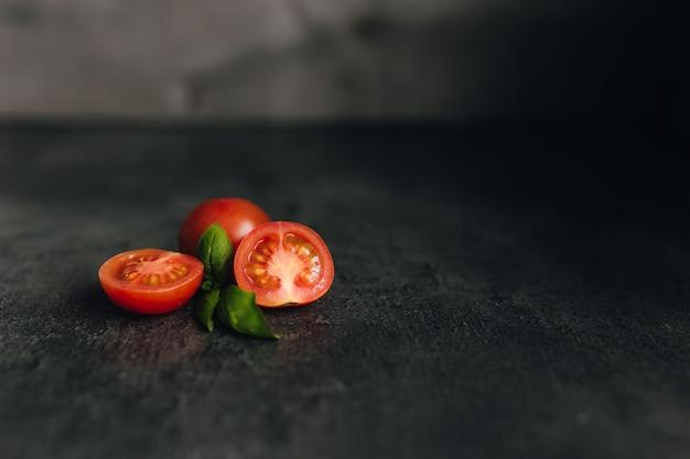 Rote kirschtomaten mit grünem basilikum auf grauem hintergrund. hochwertiges foto